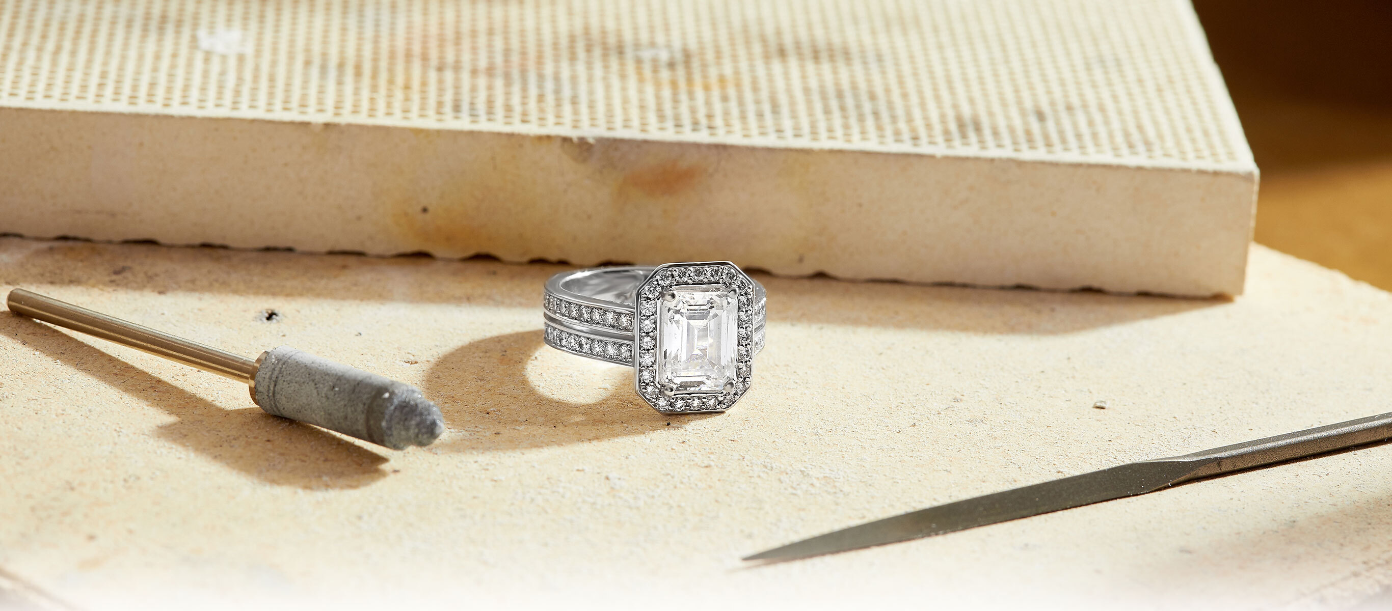 The Ecksand Pavé Emerald Cut Diamond Halo Engagement Ring with Double Diamond Band in Jewelry Workshop