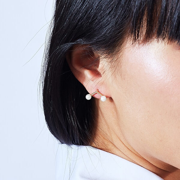 Model Wearing the Ecksand Pure Pearl V-Shaped Pearl Stud Earrings in Yellow Gold
