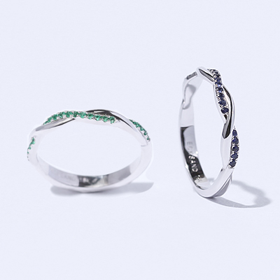 Two Ecksand Twist Intertwined Rings in White Gold Featuring Emerald Pavé and Blue Sapphire Pavé