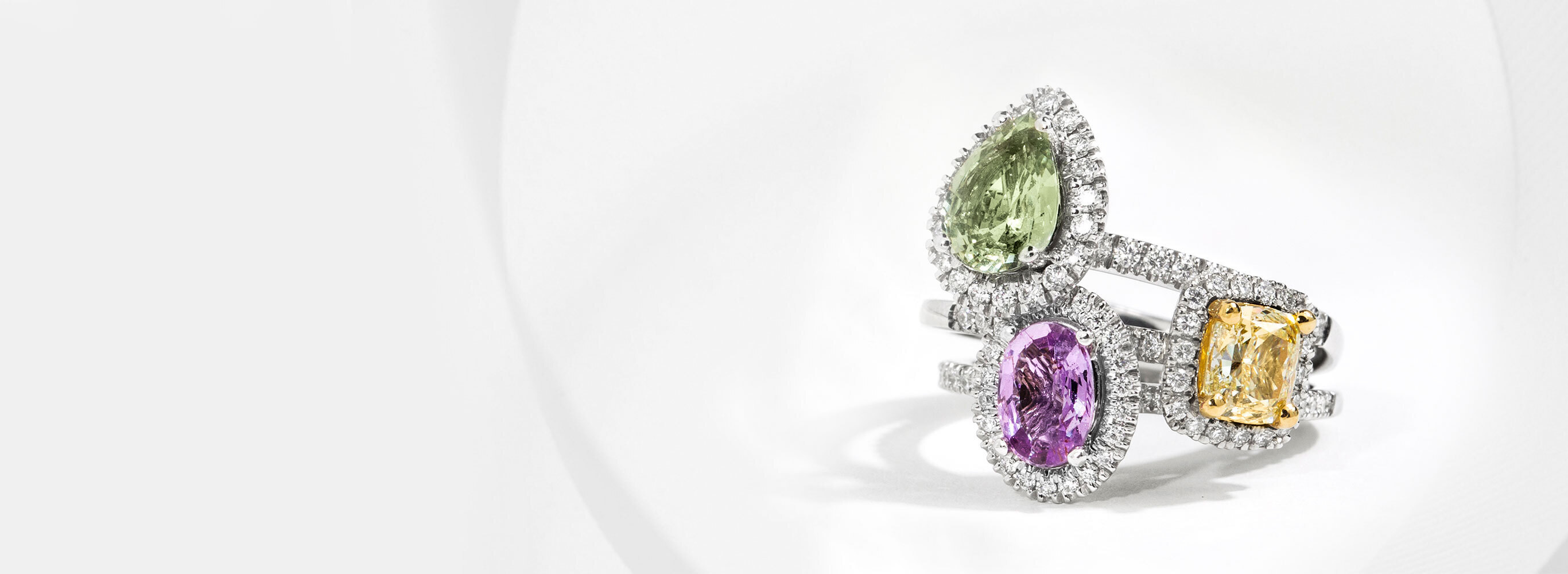 Stack of Three Diamond Halo Gemstone Engagement Rings In White Gold Featuring Pear Cut Green Sapphire, Cushion Cut Yellow Sapphire, and Oval Cut Violet Sapphire