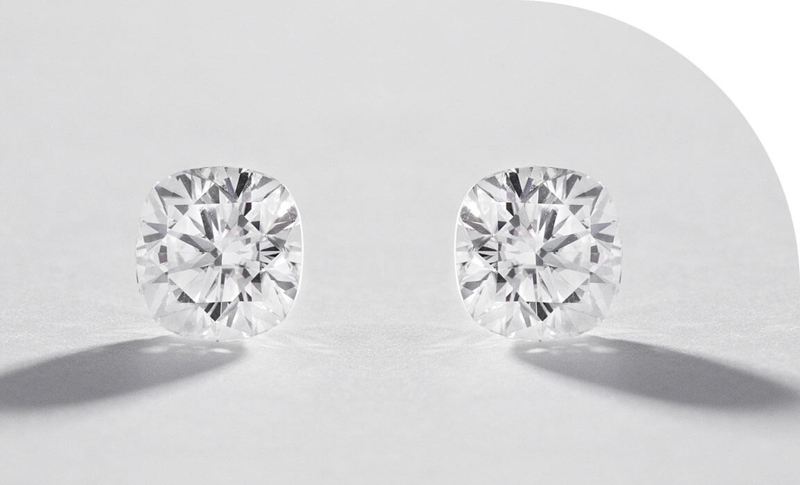 A Pair of Loose Round Cut Lab-Created Diamonds on a White Table