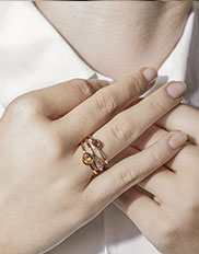 Model wearing Ecksand Showcase Stackable Rings in Yellow Gold Featuring Round Cut Garnet, Oval Cut Diamond, and Round Cut Yellow Sapphire