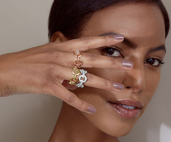 Model Wearing Ecksand Tresses Bar Stud Earrings and Thin Stackable Ring in Yellow Gold, Ecksand Pure Custom Signet Ring and Flower Ring in Yellow Gold