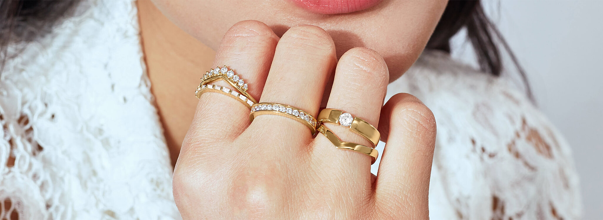 Model wearing 5 Ecksand rings in yellow gold with diamonds