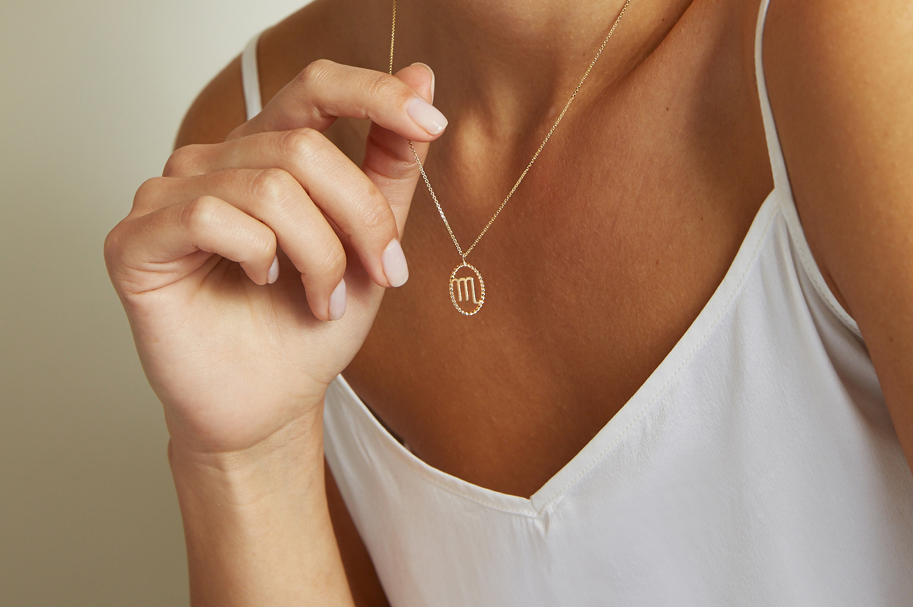 Model Wearing the Ecksand Tresses Gold Zodiac Necklace in Yellow Gold