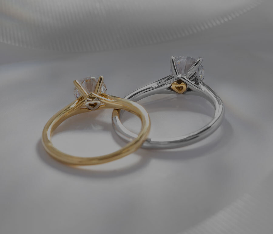 Pair of Ecksand Secret Heart Round Cut Diamond Solitaire Engagement Rings with Secret Gold Heart in White Gold and Yellow Gold