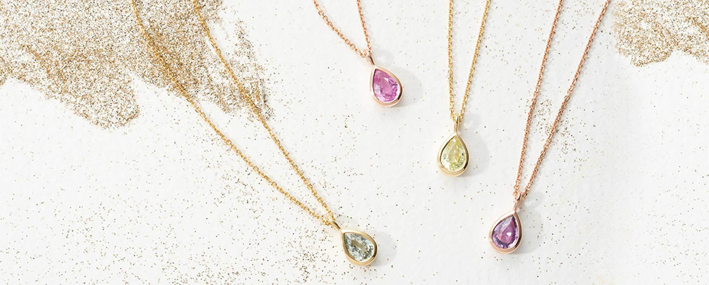 Four Ecksand Showcase Pear Cut Sapphire Gemstone Necklaces in Yellow Gold featuring Blue Sapphire, Pink Sapphire, Green Sapphire, and Purple Sapphire