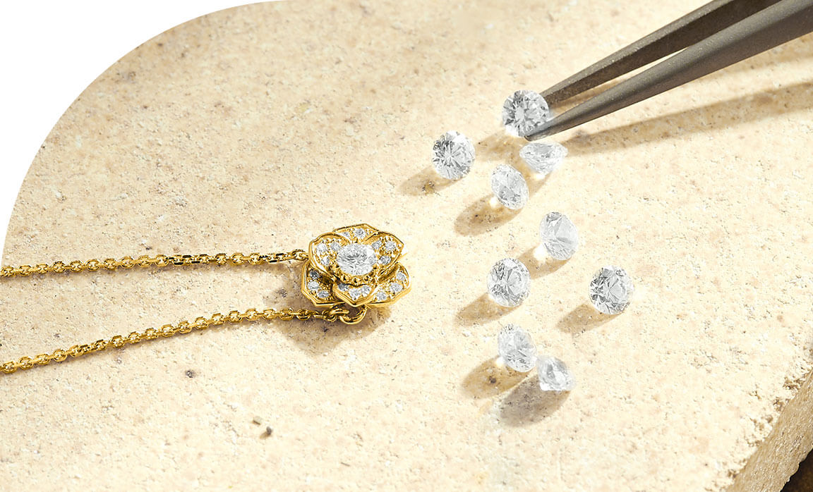 An Ecksand Jeweller Placing Loose Round Cut Diamonds into the Ecksand Blossom Diamond Pavé Flower Necklace