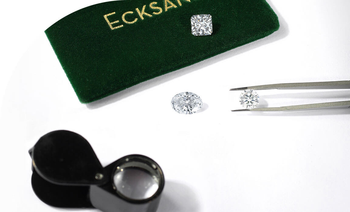 An Ecksand Jeweller Inspecting two Loose Round Cut Diamond and a Loose Cushion Cut Diamond with a Jewellers Loupe and a Large Green Ecksand Jewellery Pouch
