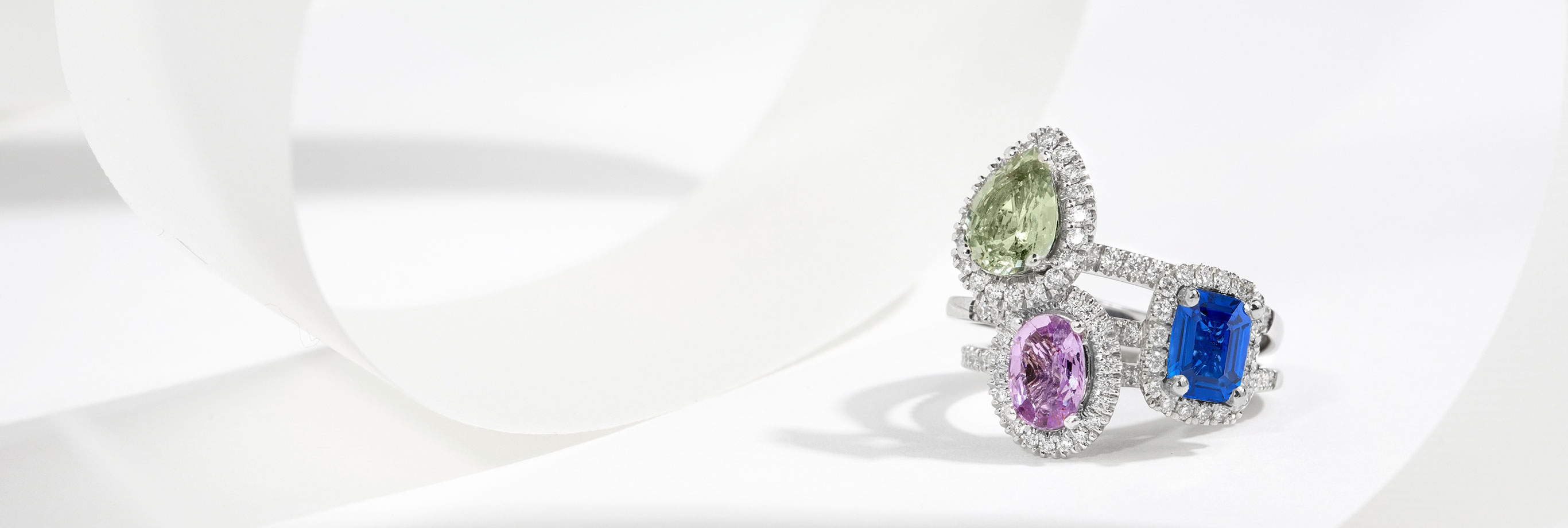 Stack of Three Diamond Halo Gemstone Engagement Rings In White Gold Featuring Pear Cut Green Sapphire, Emerald Cut Blue Sapphire, and Oval Cut Violet Sapphire