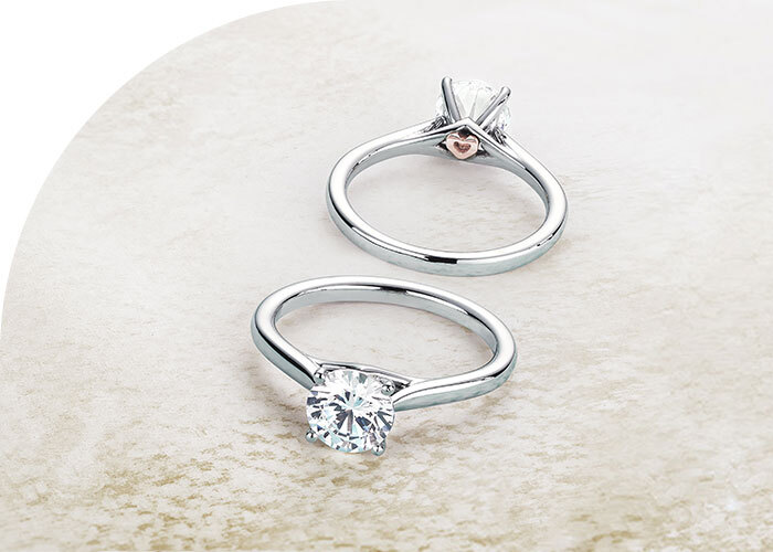 Two Ecksand Secret Heart Round Cut Diamond Engagement Rings in White Gold featuring Rose Gold Heart Beneath the Centre Diamond