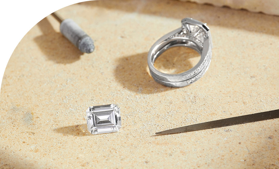 The Ecksand Pavé Halo Emerald Diamond with Double Diamond Band, a Loose Emerald Cut Lab-Created Diamond, Diamond Tweezers, and a Diamond Polishing Pad in the Ecksand Atelier