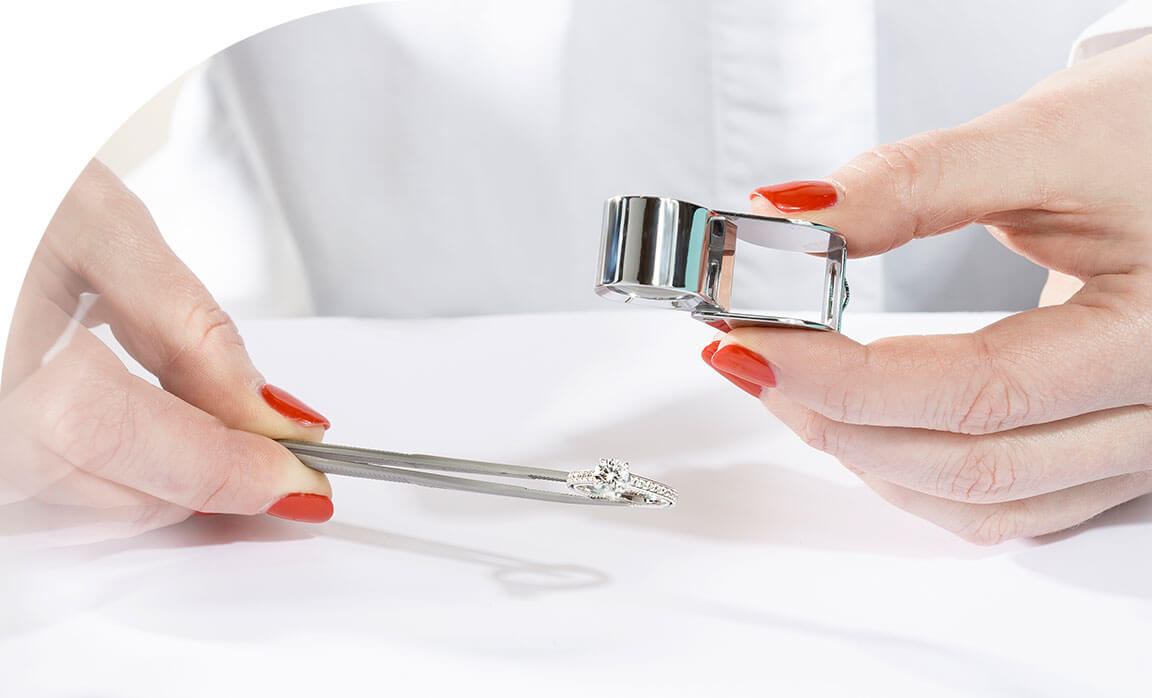 An Ecksand Jeweller Inspecting the Ecksand Pavé Round Cut Diamond Engagement Ring with Diamond Band with a Jewellers Loupe