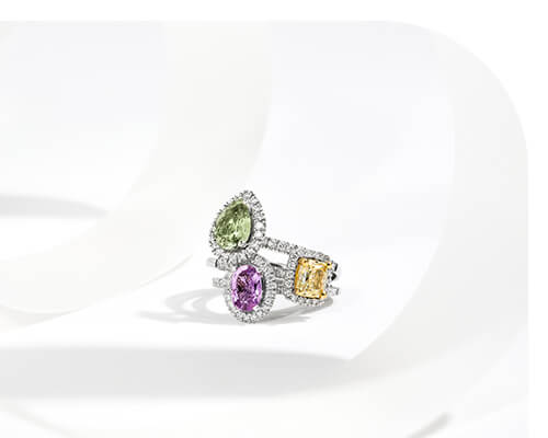 Stack of Three Ecksand Gemstone Halo Engagement Rings in White Gold Featuring Pear Cut Green Sapphire, Cushion Cut Yellow Diamond, and Oval Cut Violet Sapphire