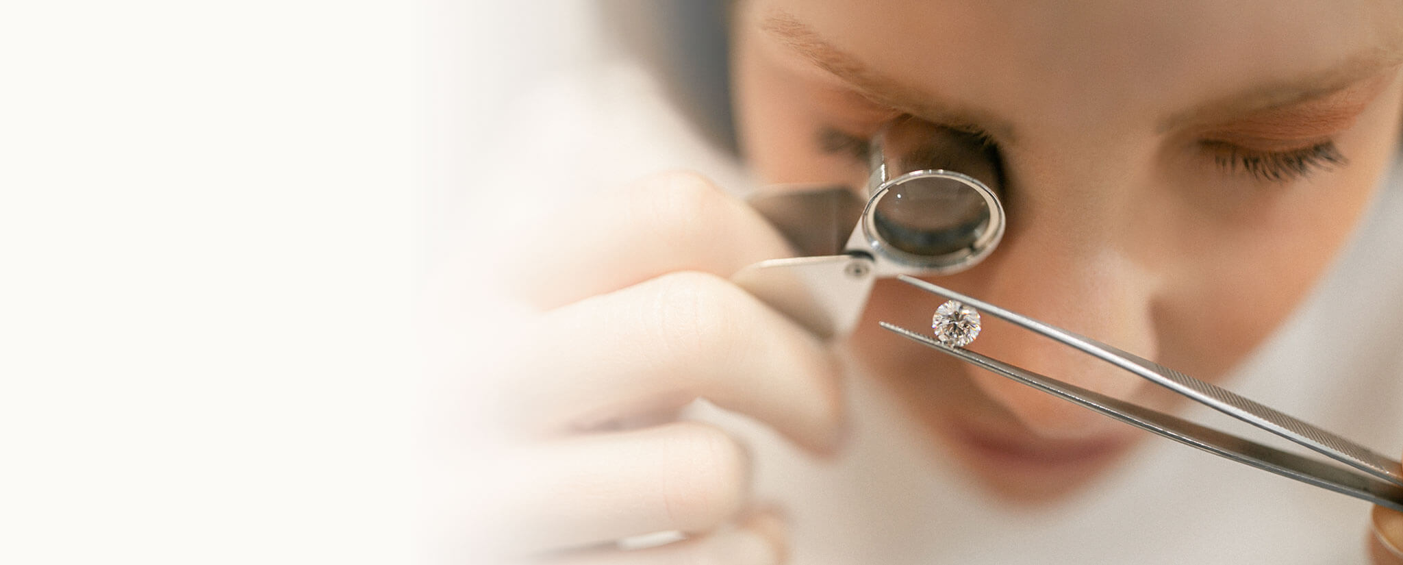 An Ecksand Jeweller Inspecting a Loose Round Cut Recycled Diamond Held in a Pair of Diamond Tweezers Through a Jewellers Loupe